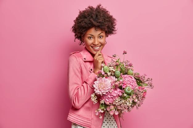 Fröhliche zarte junge afroamerikanische frau in hochstimmung, bekommt hübsche blumen, genießt schönes geschenk, lächelt breit, posiert drinnen. ein glücklicher lehrer erhält am tag des wissens einen blumenstrauß von den schülern