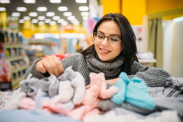 Fröhliche zukünftige mutter in gläsern kauft babykleidung im laden für neugeborene.