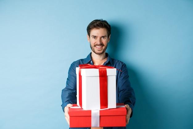 Fröhlichen valentinstag. hübscher mann, der freundin geschenke gibt, geschenkboxen hält und lächelt, über blauem hintergrund stehend.