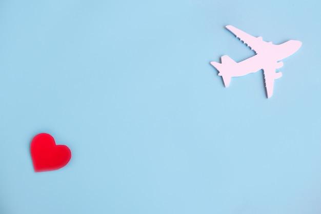 Fröhlichen valentinstag. kinderflugzeug auf einem blauen hintergrund mit rotem herzen