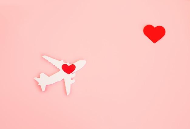 Fröhlichen valentinstag. kinderflugzeug auf einem rosa hintergrund mit rotem herzen