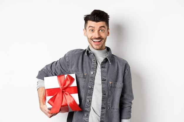 Fröhlichen valentinstag. überraschter und glücklicher kerl, der geschenkbox hält und in die kamera schaut, erstaunt lächelt, urlaub feiert, geschenk zu einem romantischen date mitbringen, weißer hintergrund
