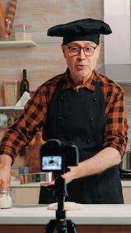 Fröhlicher älterer bäckermann, der den koch-vlog in der heimischen küche filmt. pensionierter blogger-koch-influencer, der internet-technologie verwendet, kommuniziert und blogging in sozialen medien mit digitaler ausrüstung fotografiert