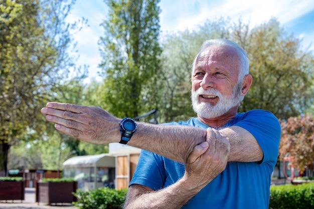 Fröhlicher älterer kaukasischer mann, der seinen arm ausstreckt, während er im park trainiert