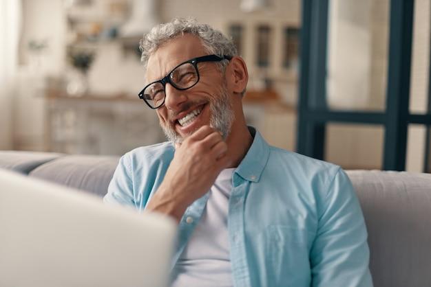 Fröhlicher älterer mann in freizeitkleidung und brille mit laptop und lächelnd, während er zu hause auf dem sofa sitzt