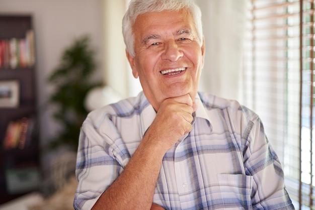 Fröhlicher älterer mann in seinem wohnzimmer