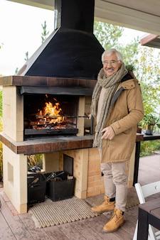 Fröhlicher älterer mann in warmer freizeitkleidung, der auf der terrasse neben seinem landhaus am kamin steht und sie beim genießen des wochenendes ansieht