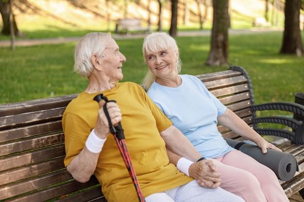 Fröhlicher älterer mann und frau mit sportgeräten ruhen auf der bank im park