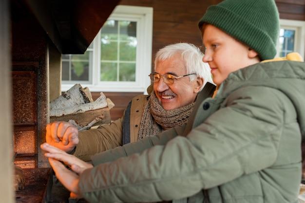 Fröhlicher älterer mann und sein enkel stehen am kamin mit brennendem brennholz, während sie sich an einem kühlen herbsttag im landhaus warm werden
