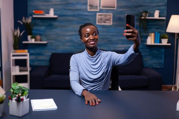 Fröhlicher afrikaner, der das smartphone anschaut, das selfie mit blick auf die frontkamera macht. beschäftigter fokussierter freiberufler, der moderne drahtlose netzwerktechnologie verwendet und überstunden macht.