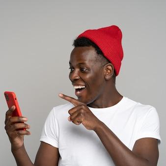 Fröhlicher afrikanischer hipster-mann tragen roten hut, der in den sozialen medien plaudert und lacht