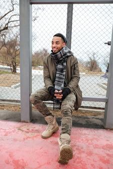 Fröhlicher afrikanischer mann, der handy benutzt und draußen lächelt