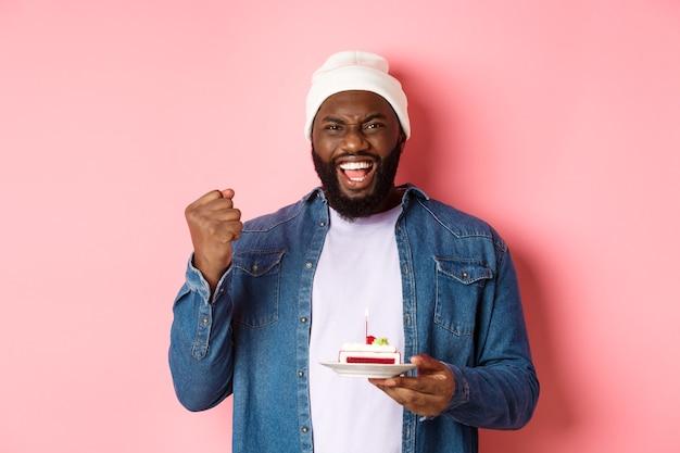 Fröhlicher afroamerikaner, der geburtstag feiert, wunsch auf bday kuchen mit beleuchteter kerze macht, glücklich lächelt und über rosa hintergrund steht