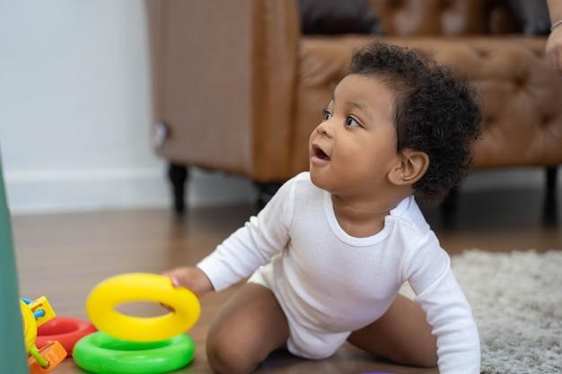 Fröhlicher afroamerikaner kleines baby, das krabbelt und nach etwas zu lernen sucht