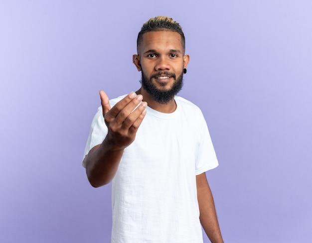 Fröhlicher afroamerikanischer junger mann im weißen t-shirt, der die kamera anschaut, lächelt freundlich und macht hierher geste mit der hand, die über blauem hintergrund steht