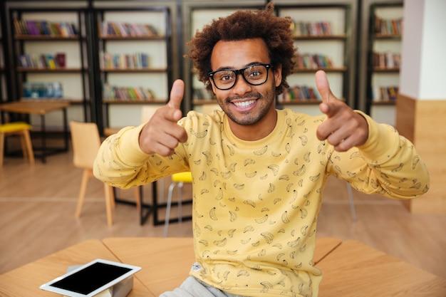 Fröhlicher afroamerikanischer junger mann mit brille, der in der bibliothek auf sie sitzt und auf sie zeigt