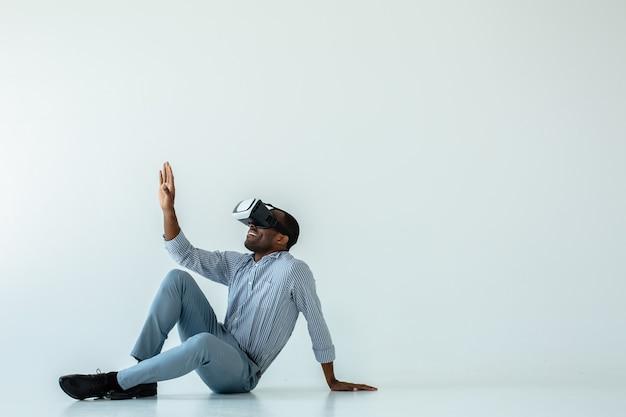 Fröhlicher afroamerikanischer mann, der auf dem boden sitzt, während vr brille testend