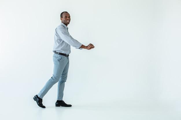 Fröhlicher afroamerikanischer mann, der einen supermarkt besucht, während er mit dem wagen geht