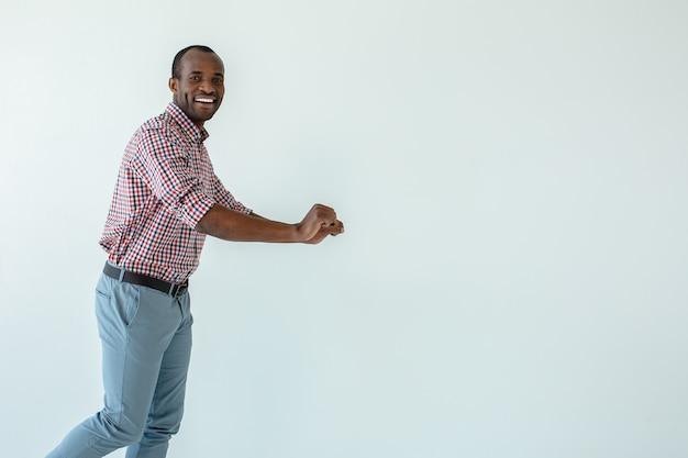 Fröhlicher afroamerikanischer mann, der entlang der rohstoffe im supermarkt geht, während das einkaufen genießt