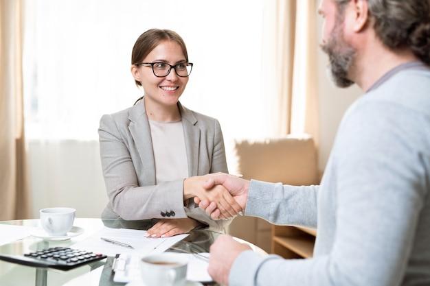 Fröhlicher agent mit zahnigem lächeln, der den kunden ansieht, während beide nach der verhandlung über den tisch schütteln