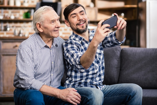 Fröhlicher alter mann, der mit seinem sohn, der selfies macht, auf dem sofa sitzt
