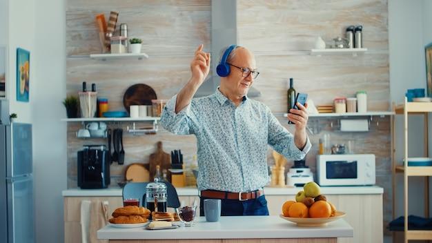 Fröhlicher alter mann tanzt in der küche und hört musik mit kopfhörern während des frühstücks. älterer rentner, der einen modernen, fröhlichen lebensstil genießt, entspannt tanzt, lächelt und moderne technologie verwendet
