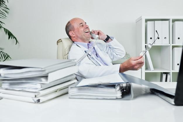 Fröhlicher arzt, der am telefon anruft