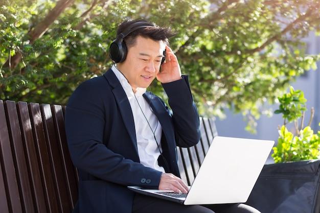 Fröhlicher asiatischer geschäftsmann, der auf einer bank in einem stadtpark in der innenstadt sitzt und mit einem laptop musik über kopfhörer hört. ein mann im anzug genießt die natur. entspannen sie sich und ruhen sie sich aus. lebensstil