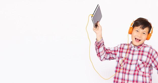 Fröhlicher asiatischer junge trägt kopfhörer und spielt das handy auf grauer oberfläche, hört musik lächeln gesicht banner kopie raum