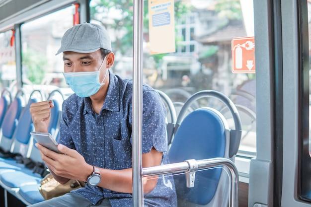 Fröhlicher asiatischer mann, der feiert, während er im öffentlichen bus mit maske auf das smartphone schaut