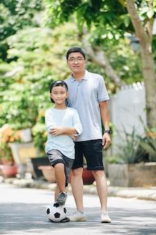 Fröhlicher asiatischer mann mittleren alters, der sohn umarmt, wenn sie zusammen posieren, nachdem sie fußball auf der straße gespielt haben