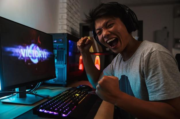 Fröhlicher asiatischer spielerjunge, der sich über den sieg freut, während er videospiele am computer in einem dunklen raum spielt, kopfhörer trägt und eine hintergrundbeleuchtete bunte tastatur verwendet