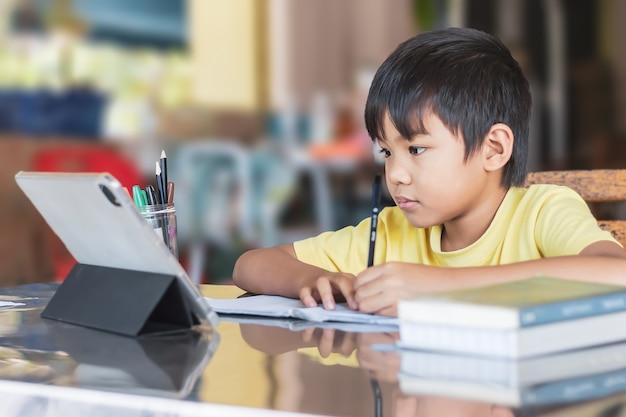 Fröhlicher asiatischer studentenjunge, der smart pad oder tablet für seine hausaufgaben verwendet und berührt
