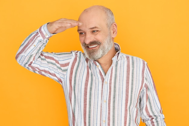 Fröhlicher attraktiver älterer mann mit grauem bart und kahlem kopf posiert isoliert und hält die hand über seine augen, um sich selbst zu schützen
