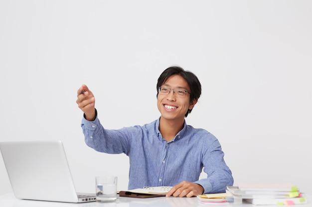 Fröhlicher attraktiver asiatischer junger geschäftsmann in den gläsern, die in notizbuch schreiben und zur seite von hand am tisch über weißer wand zeigen
