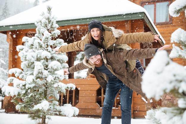 Fröhlicher attraktiver bärtiger mann, der seine freundin huckepack trägt und im winter spaß hat