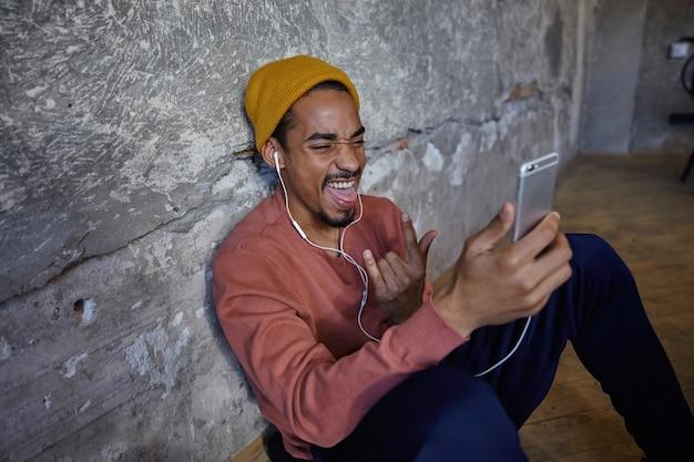 Fröhlicher attraktiver dunkelhäutiger mann mit bärtigem selfie mit seinem smartphone, der die zunge herausstreckt und das gesicht stirnrunzelt, während er über die betonwand posiert