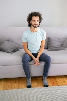 Fröhlicher attraktiver junger mann mit lockigem haar, der lässiges t-shirt trägt, zu hause auf der couch sitzt, wegschaut und lächelt. vertikaler schuss. männliches porträtkonzept