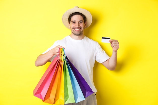 Fröhlicher attraktiver kerl, der einkaufstüten und kreditkarte, bankkonzept und einfache zahlung zeigt, auf gelbem hintergrund stehend