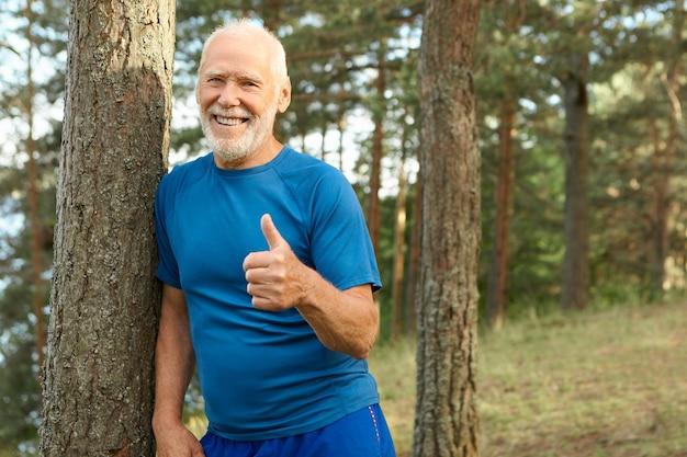 Fröhlicher attraktiver pensionierter mann mit glatze und grauem bart, der draußen in sportkleidung posiert, die glücklich lächelt, daumen hoch geste zeigt, aktiven gesunden lebensstil wählt, voller energie