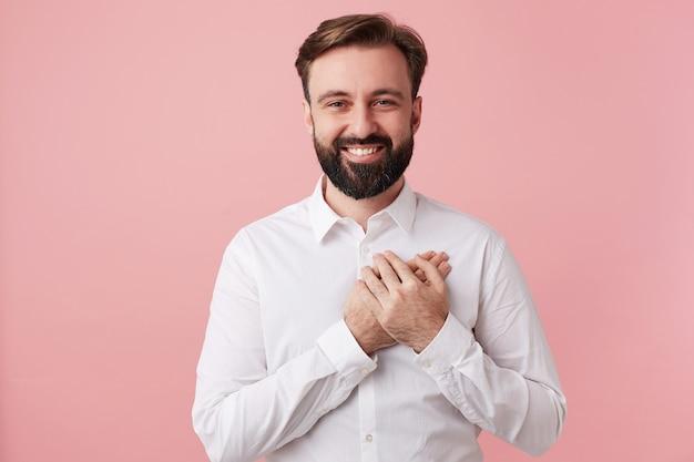 Fröhlicher attraktiver unrasierter dunkelhaariger kerl mit kurzem haarschnitt, der handfläche auf seinem herzen hält
