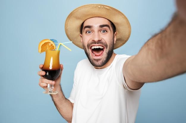 Fröhlicher aufgeregter mann mit leerem t-shirt, der isoliert über blauer wand steht, ein selfie macht und cocktail zeigt