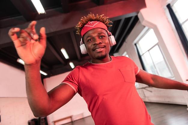 Fröhlicher aufmerksamer junger tänzer, der seine hände während der darsteller hebt, während er kopfhörer aufhat