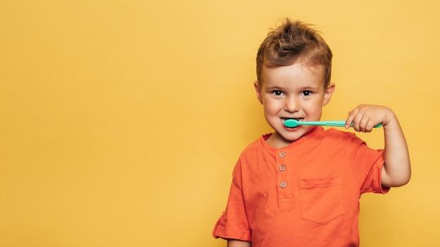 Fröhlicher baby-kleinkindjunge, der seine zähne mit einer zahnbürste auf einem gelben hintergrund putzt. gesundheitsvorsorge, mundhygiene. ein platz für ihren text.