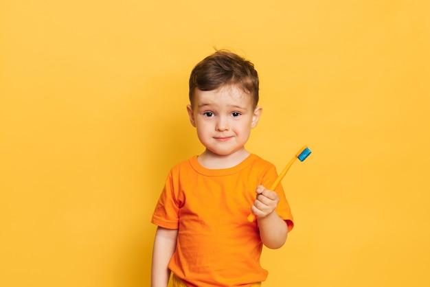 Fröhlicher baby-kleinkindjunge, der seine zähne mit einer zahnbürste auf einem gelben hintergrund putzt. gesundheitsvorsorge, mundhygiene.