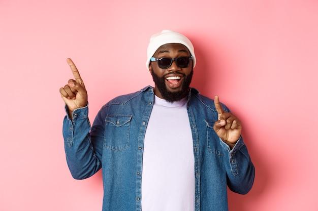 Fröhlicher bärtiger afroamerikaner, der ankündigung zeigt, mit den fingern auf die obere linke ecke zeigt und lächelt, in mütze und sonnenbrille auf rosa hintergrund steht