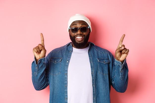 Fröhlicher bärtiger afroamerikaner, der ankündigung zeigt, mit den fingern nach oben zeigt und lächelt, in mütze und sonnenbrille auf rosa hintergrund steht