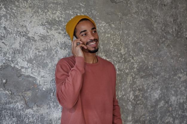 Fröhlicher bärtiger dunkelhäutiger mann mit charmanten braunen augen, die beiseite schauen und glücklich lächeln, während sie ein nettes gespräch am telefon führen