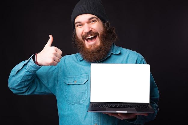 Fröhlicher bärtiger hipster-mann, der daumen oben zeigt und laptop hält