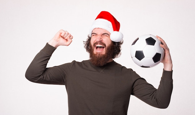 Fröhlicher bärtiger hipster-mann, der schreit und den sieg feiert und fußball hält, weihnachtsmann